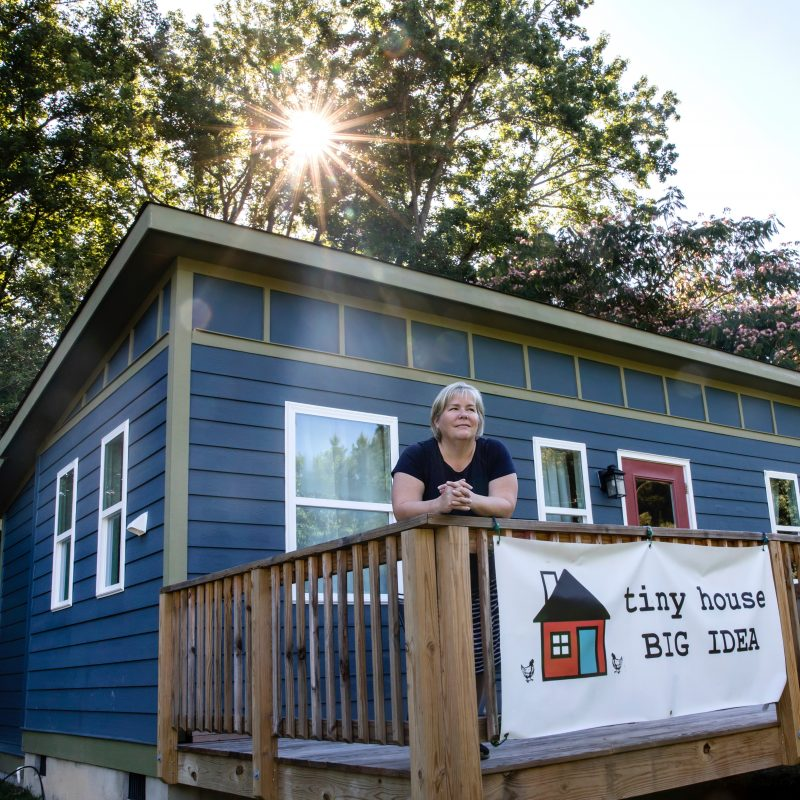 Amy Blank Wilson standing in front of a Tiny Homes Village home