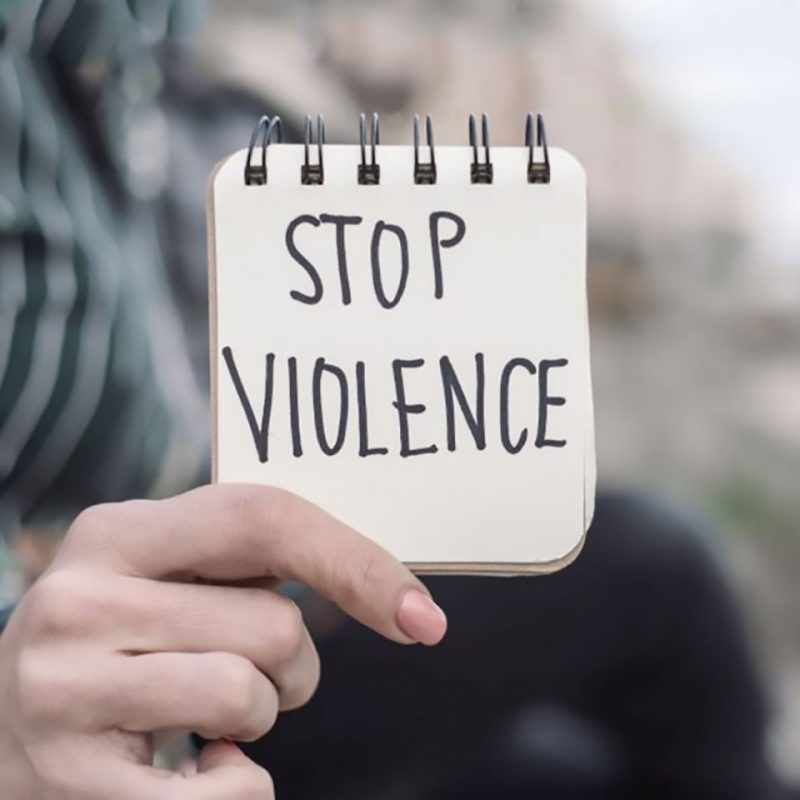 Closeup of a young caucasian woman outdoors showing a notepad with the text stop violence written in it