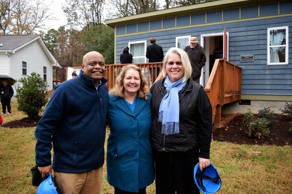 image of Tiny Homes founder Thava Mahadevan with Millie Brobston with the International Oak Foundation and social work associate professor Amy Blank Wilson.