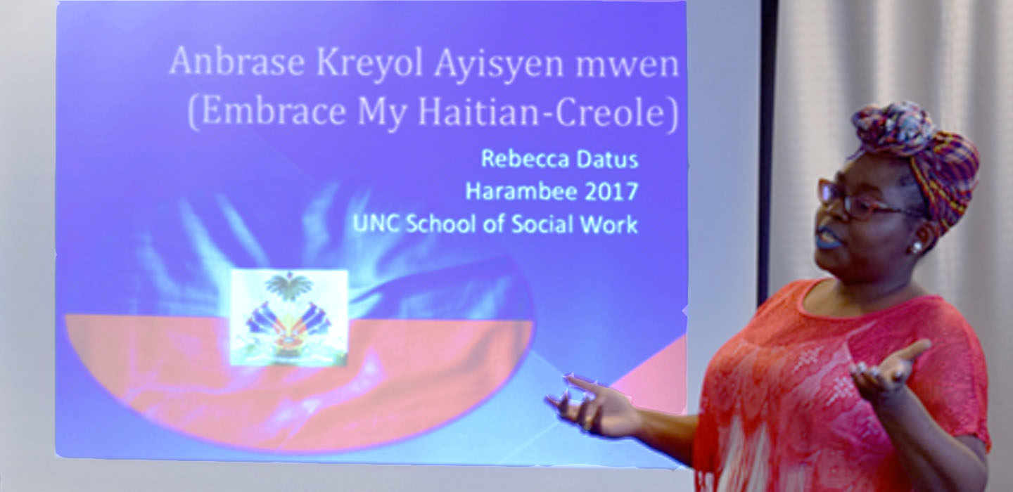 """student in red print shirt and headscarf speaks in front of screen with """"Embrace My Haitian-Creole"""" [culture] written on the slide"""