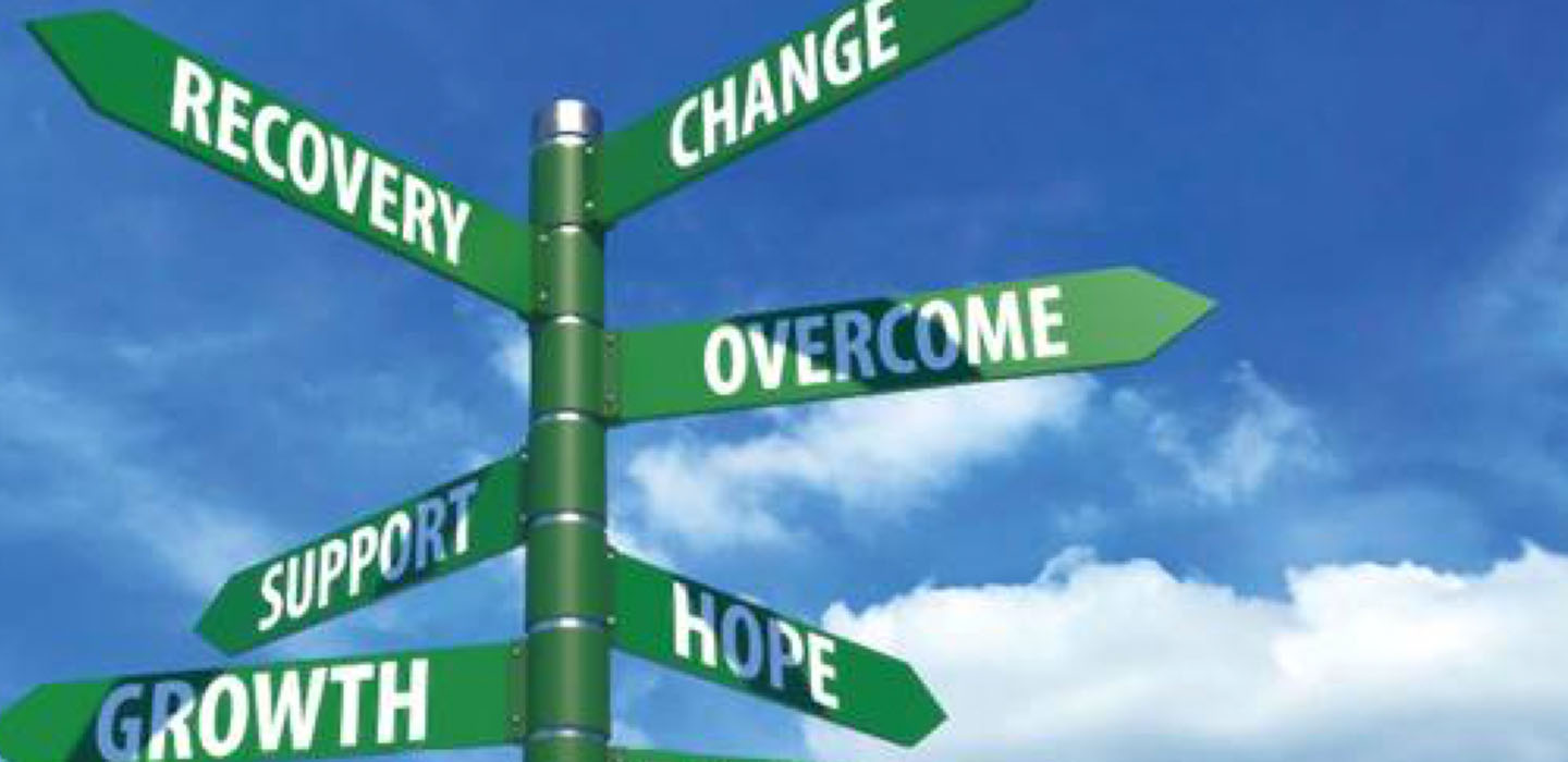 """crossroads sign against blue sky background, with directions for """"change,"""" """"overcome,"""" """"hope,"""" """"recovery"""" and """"growth"""""""