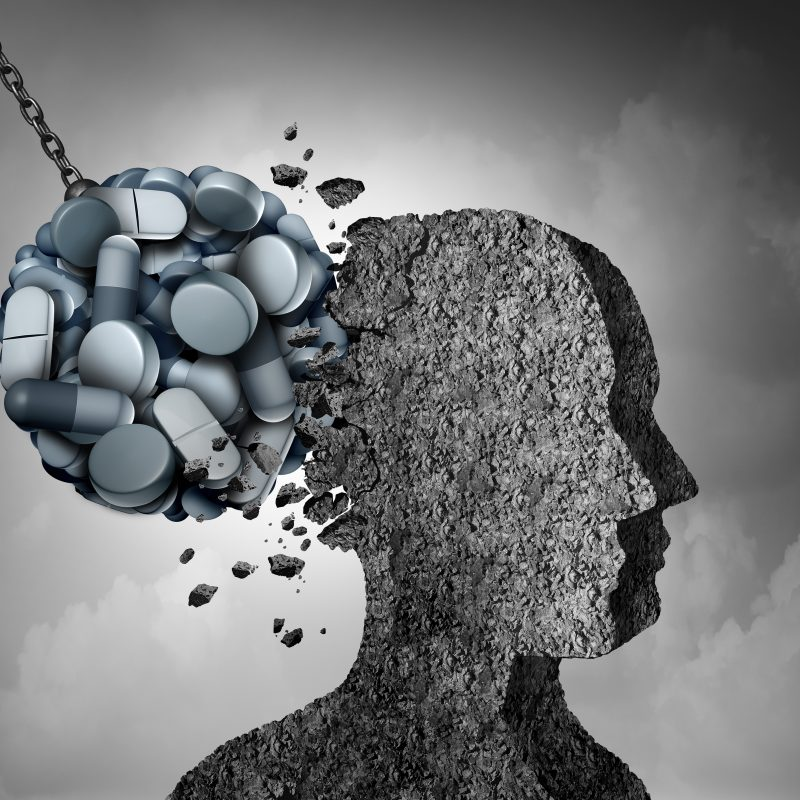 graphic of addiction depicted as pills balled up as a wrecking ball and smashing into the back of the silhouette of a person's headdiction