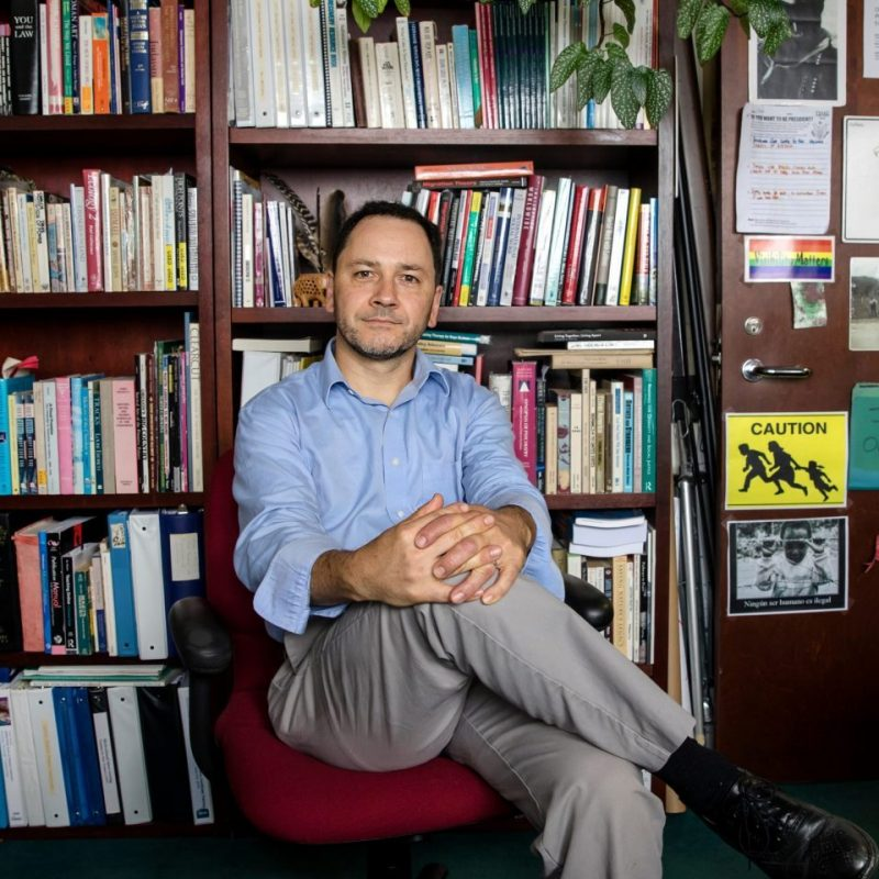 Clinical assistant professor Josh Hinson sits in front of a wall of books in his office.
