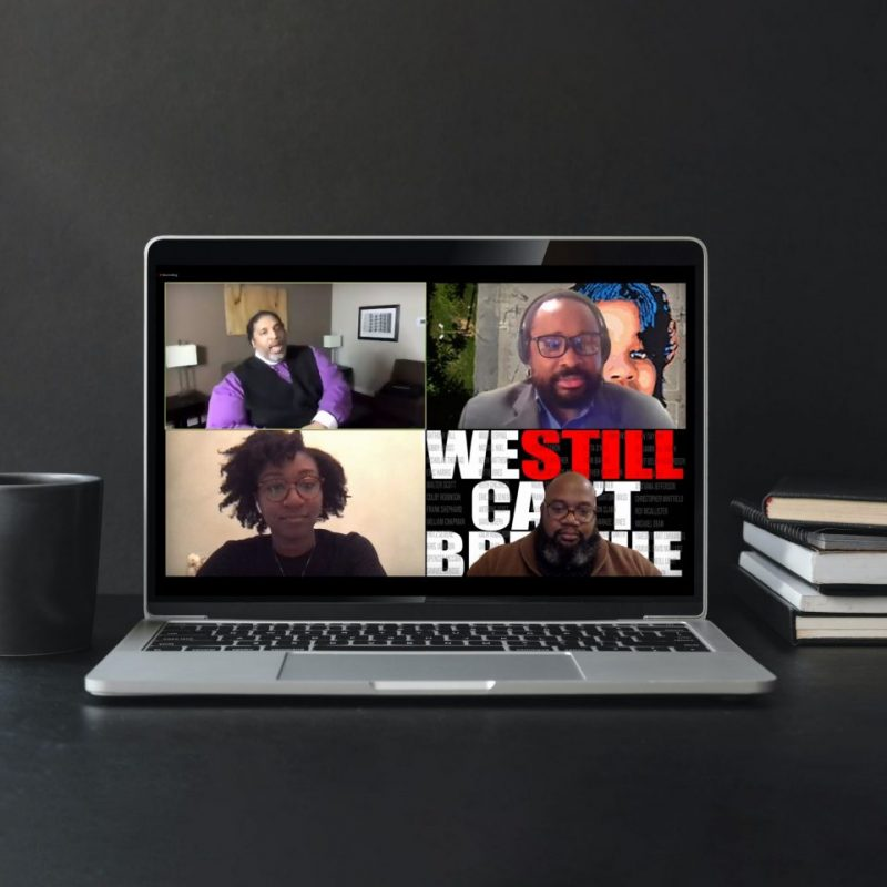 An open laptop sits on a desk with a screenshot from Rev. Barber's presentation during the first Centennial Speaker Series.