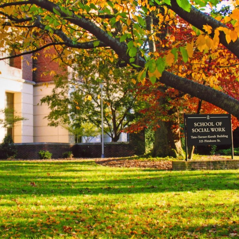 School of Social Work sign in front of a tree with fall-colored leaves.