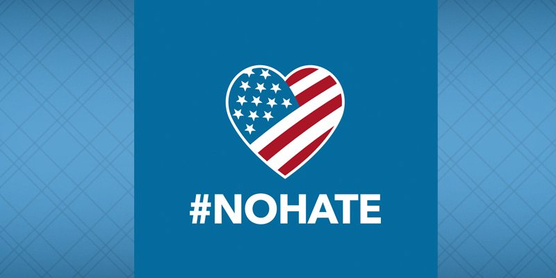 """Hate Has No Home Here icon, with blue background, heart shape filled with a """"stars and stripes"""" American flag design, and the hashtag #NOHATE"""