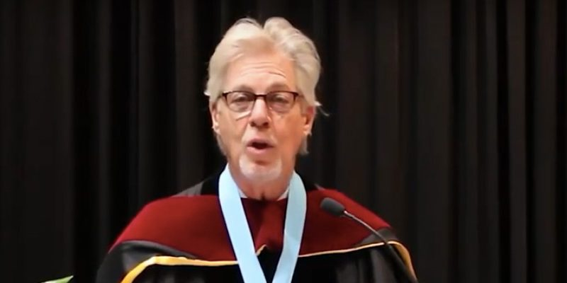 Dean Gary Bowen, wearing academic regalia, speaks at lecturn during Commencement 2021