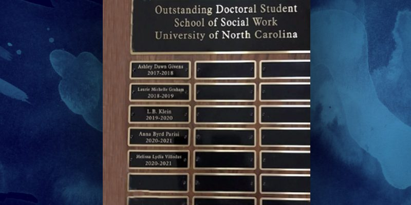 """Wooden plaque with multiple black metal nameplates, """"Outstanding Doctoral Student"""" heading on top nameplate, award winner names on three columns of smaller nameplates"""