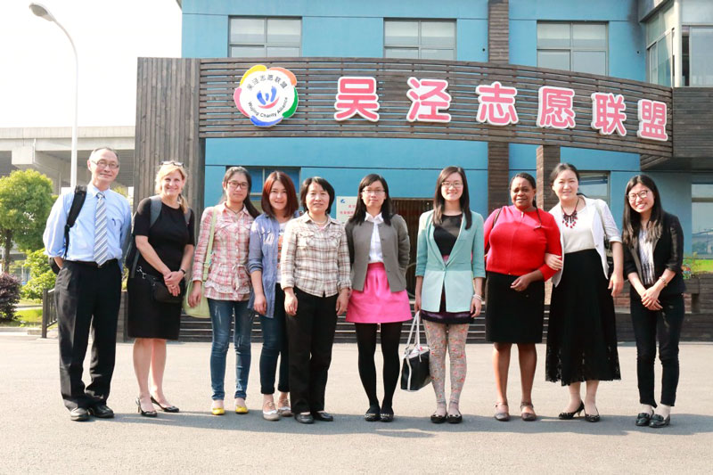 Professors Mimi Chapman and Gina Chowa stand with eight unidentified men and women in front of a blue building under a sign with Chinese characters