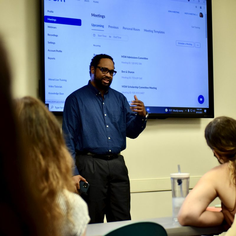Professor Travis Albritton, dressed in a blue shirt and black pants, speaks to a classroom of new MSW students.