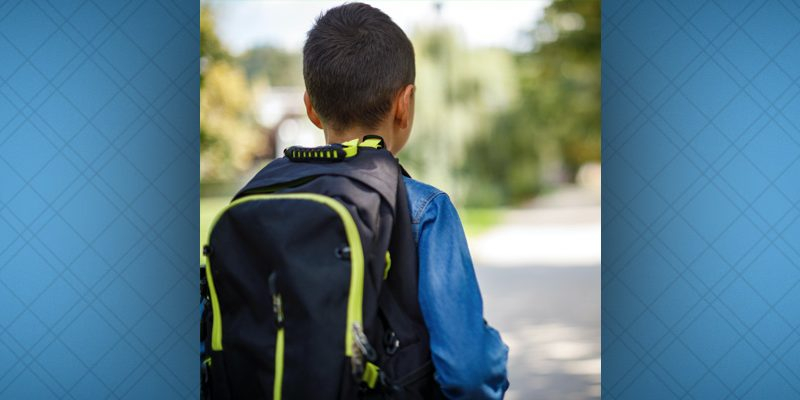 Young child with backpack looks down an empty, semi-rural street, his back to camera