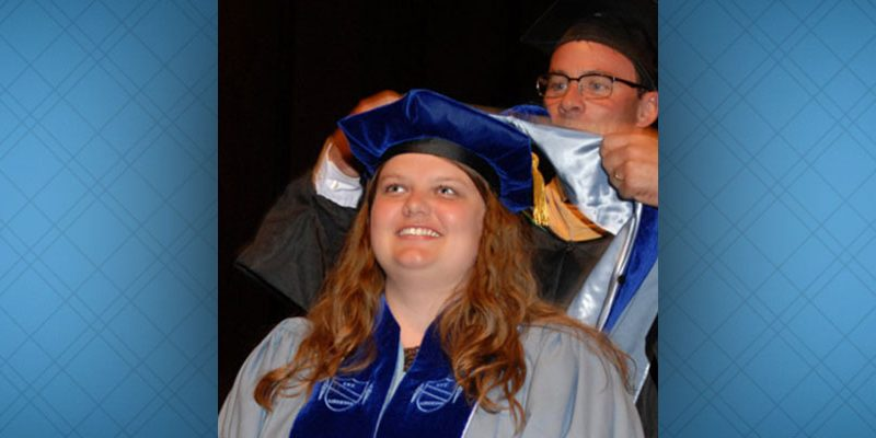 a new doctoral program graduate and a faculty member participate in the hooding ceremony during commencement